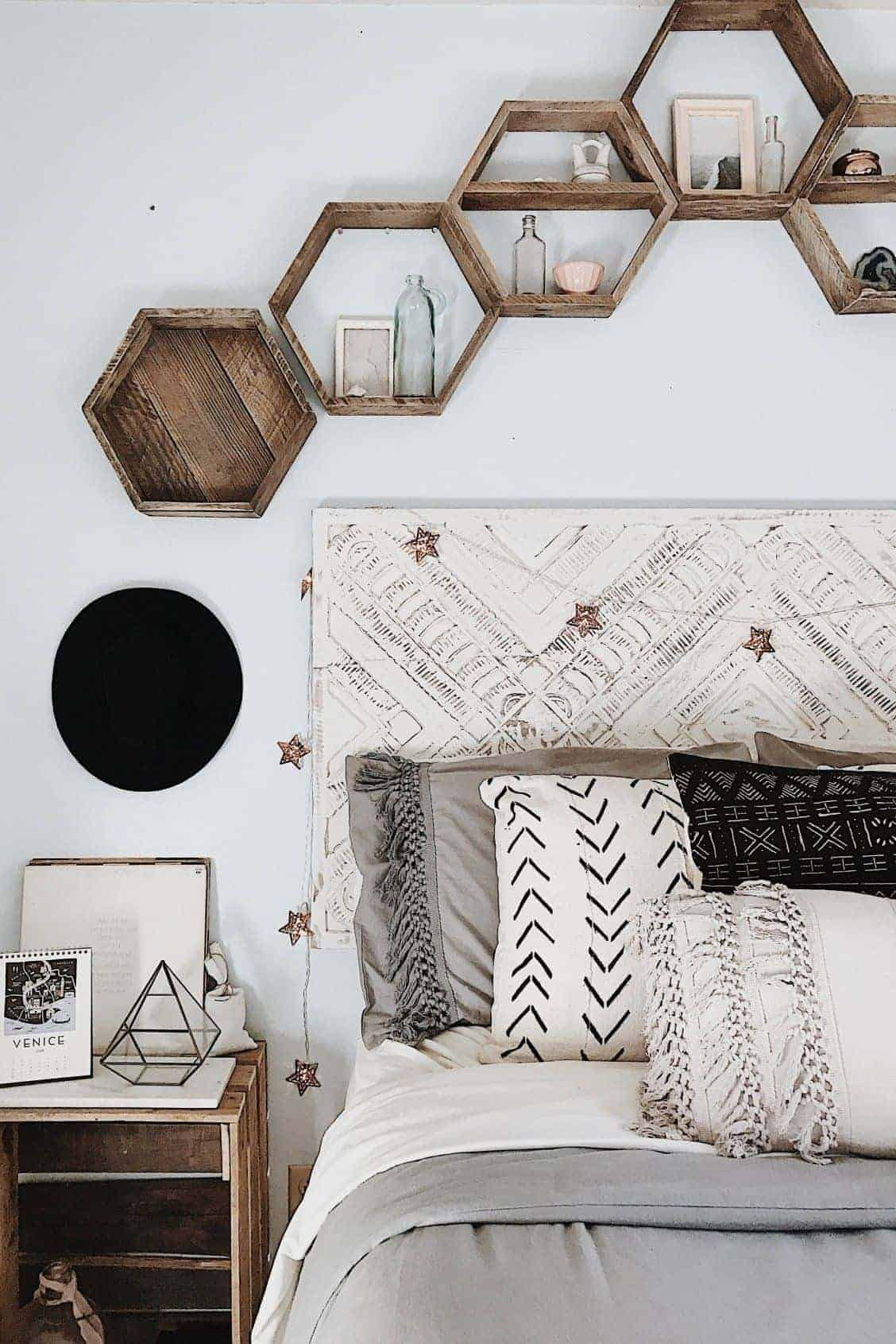 A bohemian bedroom with patterned pillow cases and a bedframe along with hexagonal floating wooden shelves hung above the bed.