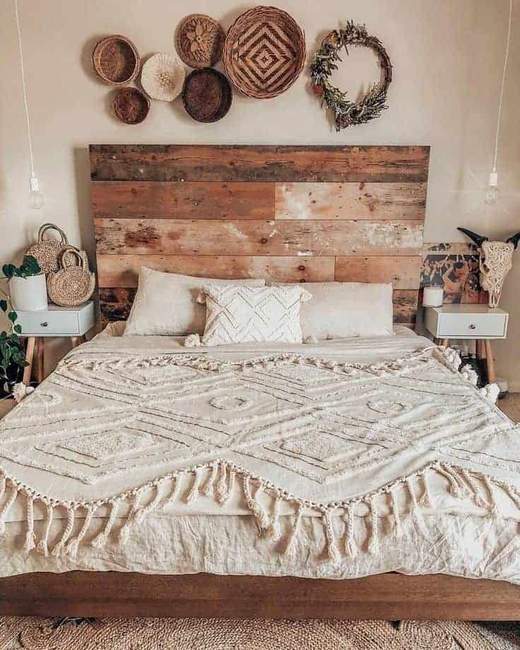 A bohemian bedroom with neutral-toned beddings, Nordic-style side tables, a tasseled cover, and woven wall décor hung above the bed.