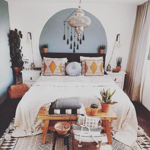 A bohemian bedroom with a comfortable bed, potted plants, and a wooden bench at the foot of the bed.