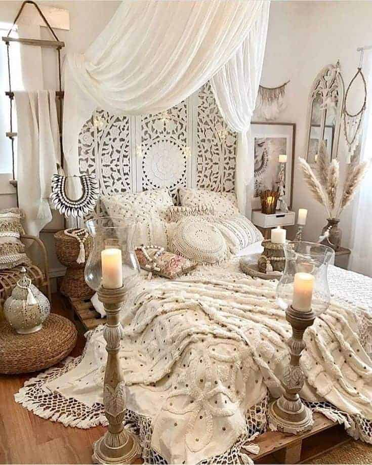 A bohemian bedroom with a white curtain overhang, a pallet platform bed, and various candleholders.