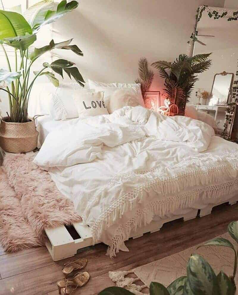 A bohemian bedroom with white beddings, indoor plants, and a tasseled bed cover.