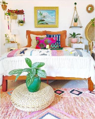 A bohemian bedroom with colorful beddings, a framed island wall art, and a natural woven ottoman.