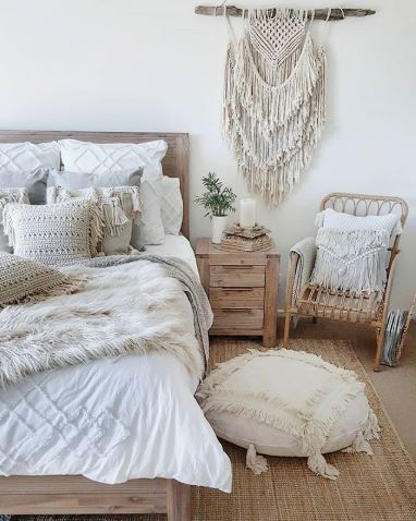 A bohemian bedroom with neutral-toned beddings, a macramé wall hanging, and light-colored bedside table.