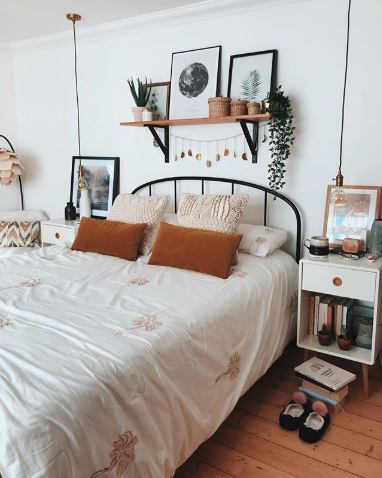 A bohemian bedroom with white sheets, tan throw pillows, and decorative pieces hung on a floating wooden shelf.