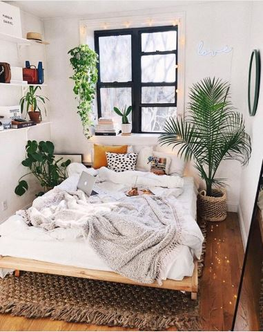 A bohemian bedroom with neutral-colored beddings, indoor plants, and a woven patterned area rug.