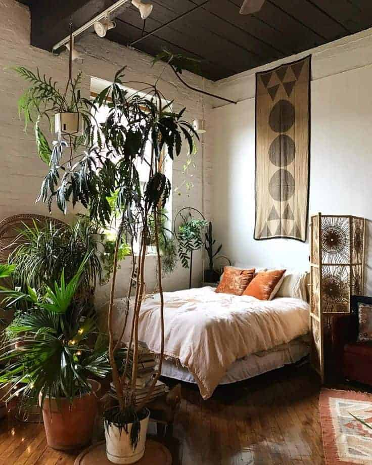 A bohemian bedroom with indoor plants, tan pillow cases, and a patterned woven partition.