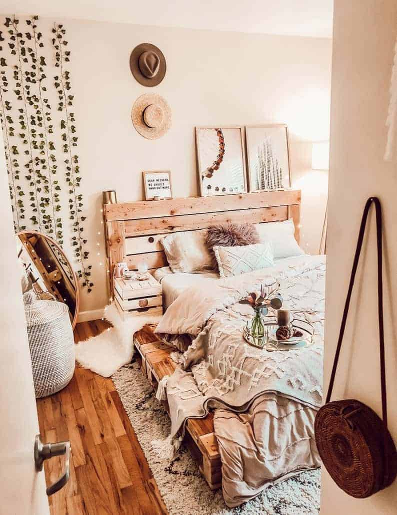 A bohemian bedroom with neutral-colored beddings, hat décor, artworks, and a wooden pallet bed to match the wooden floors.