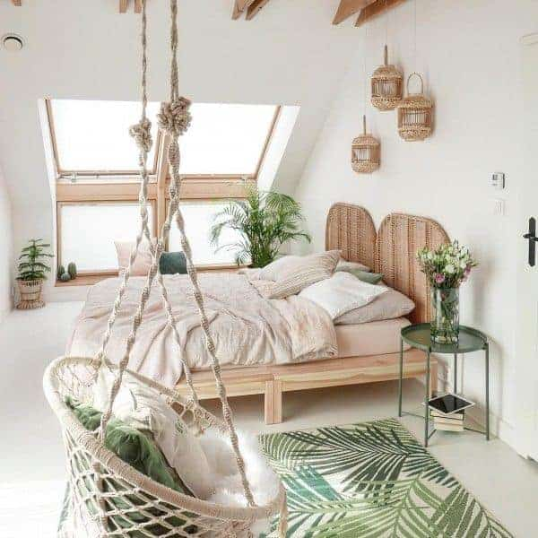 A bohemian bedroom with a light-colored wooden bed frame, woven wall décor, and an off-white rope chair.