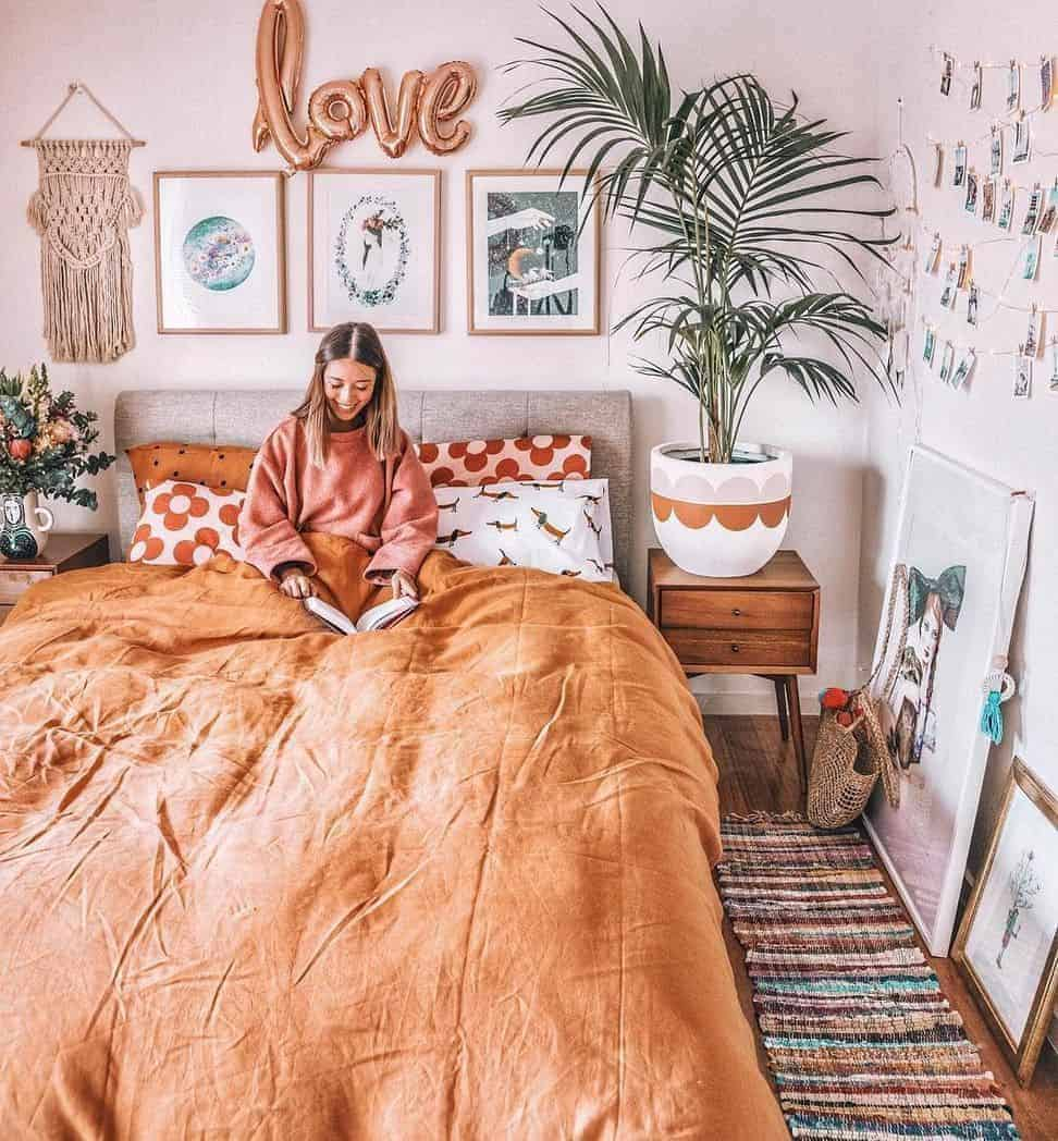 A bohemian bedroom with tan-colored beddings, and wall art accentuated by a rose gold foil balloon.
