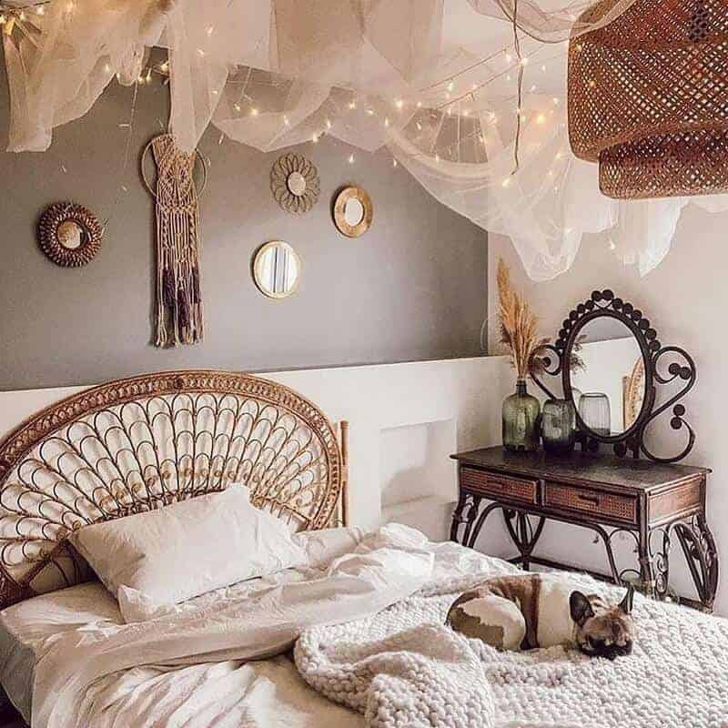 A bohemian bedroom with a woven bed frame, wall mirrors above the bed, with matching tulle fabric and fairy lights.