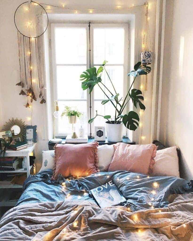 A bohemian bedroom with pink and gray beddings, fairy lights, and a large dreamcatcher hung on top of the window.