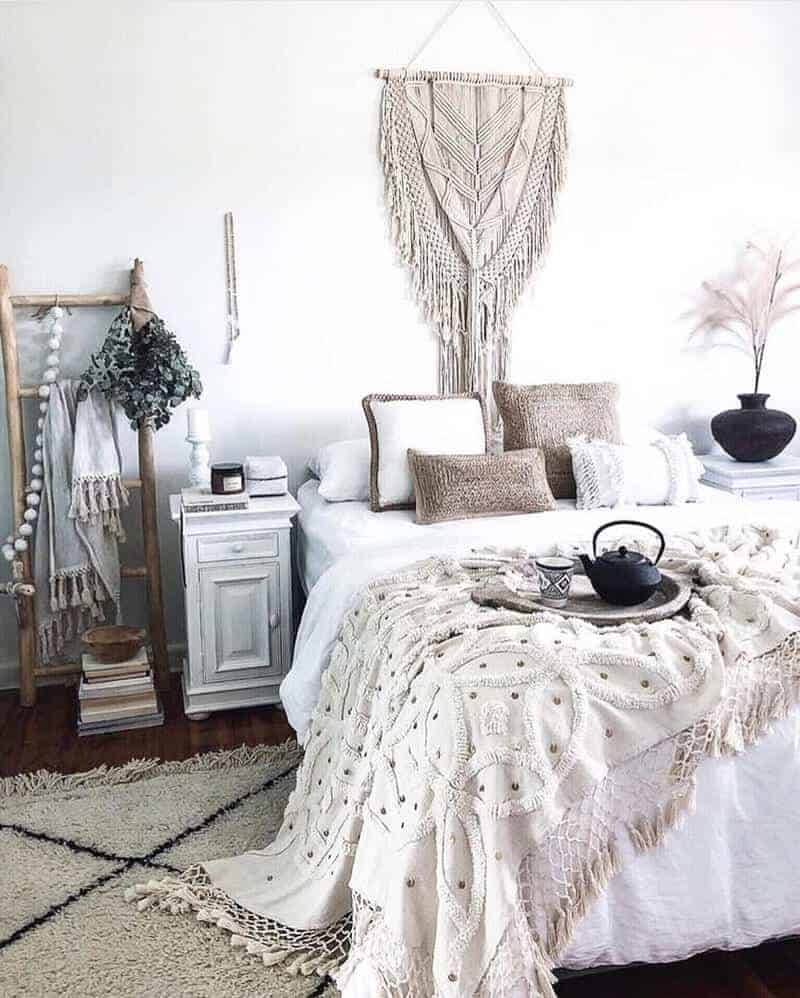 A bohemian bedroom with neutral-colored beddings, a tasseled blanket, and a macramé wall hanging above the bed.