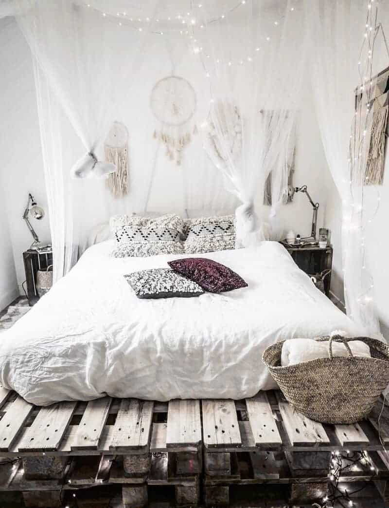 A bohemian bedroom with white sheets, dreamcatchers hung above the bed, and tufted pillow cases to accentuate the aesthetic.