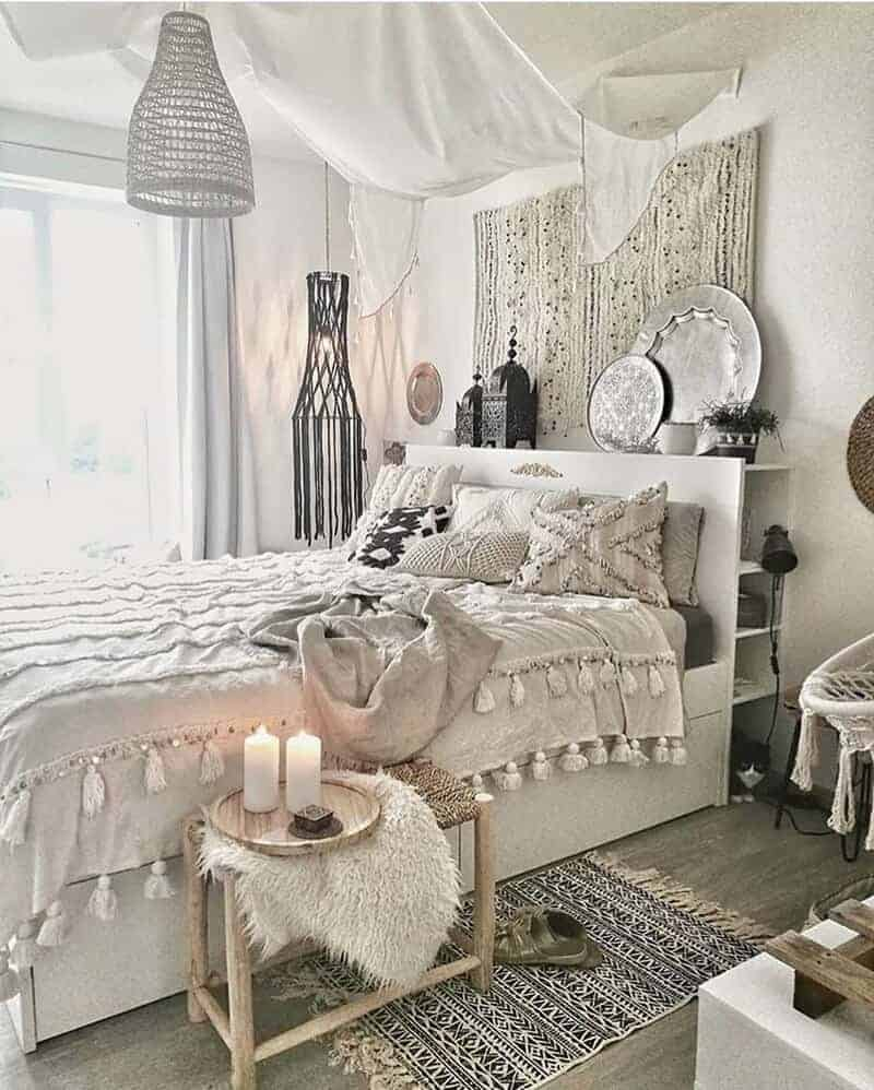 A bohemian bedroom with a white bed frame, tasseled bed cover, and matching black and white area rug.