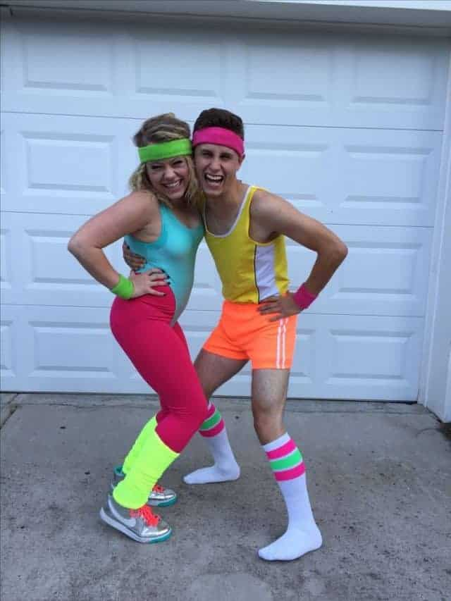 A woman and a man wearing neon-colored '80s aerobics costumes.