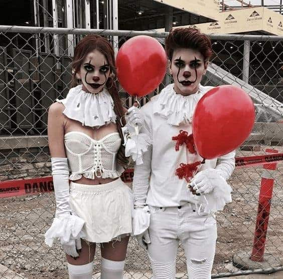 Two individuals wearing matching couple-clowns costumes inspired by the movie IT.