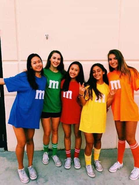 A group of women wearing M&Ms costumes in the colors blue, green, red, yellow, and orange.