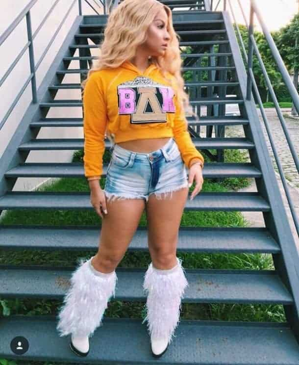 A woman wearing a Beyoncé costume with the yellow hoodie, denim shorts, and fur boots from her Coachella performance.