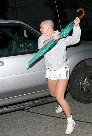 A woman wearing a Britney costume with a green umbrella inspired by one of her public meltdowns.