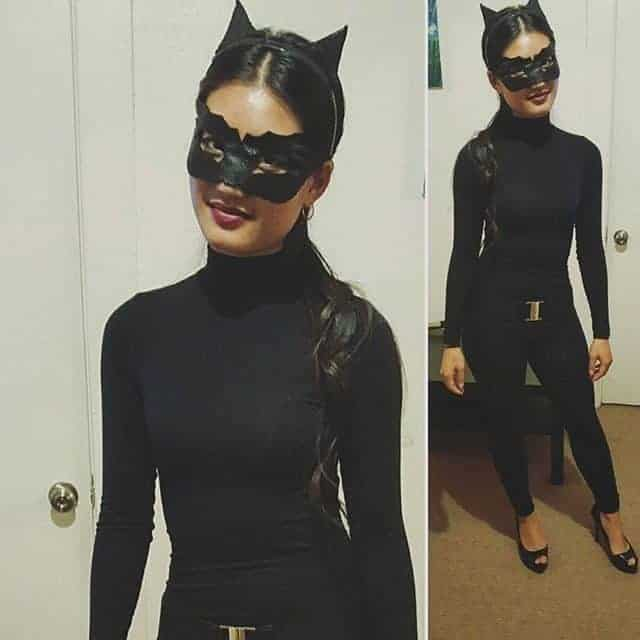 A woman wearing a black skintight Catwoman costume inspired by Chris Nolan's Batman.