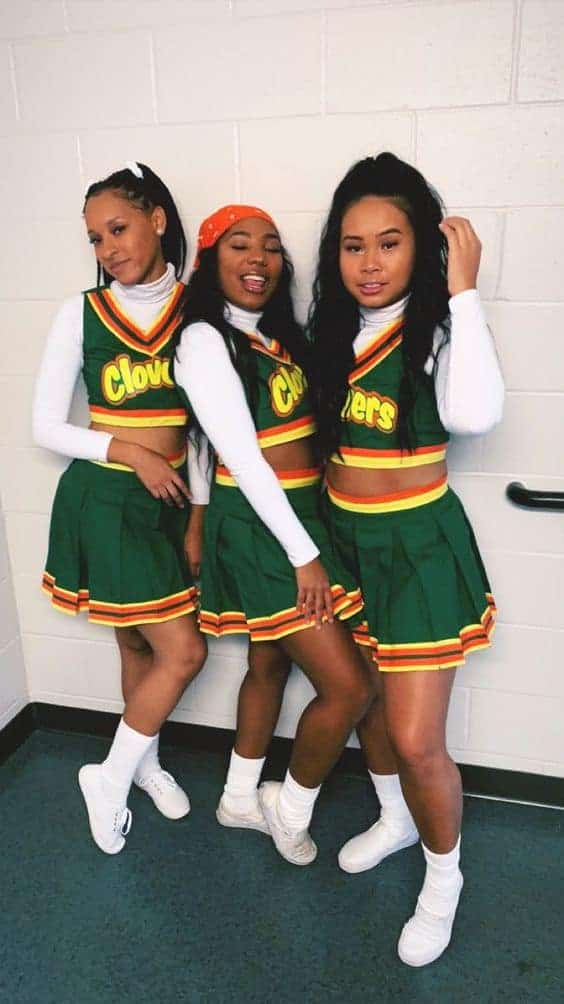 Three women wearing Clovers cheerleader costumes from the teen movie Bring It On.