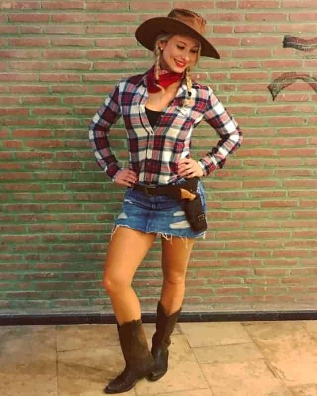 A woman wearing a cowboy costume with a plaid shirt, denim skirt, matching hat, and boots.