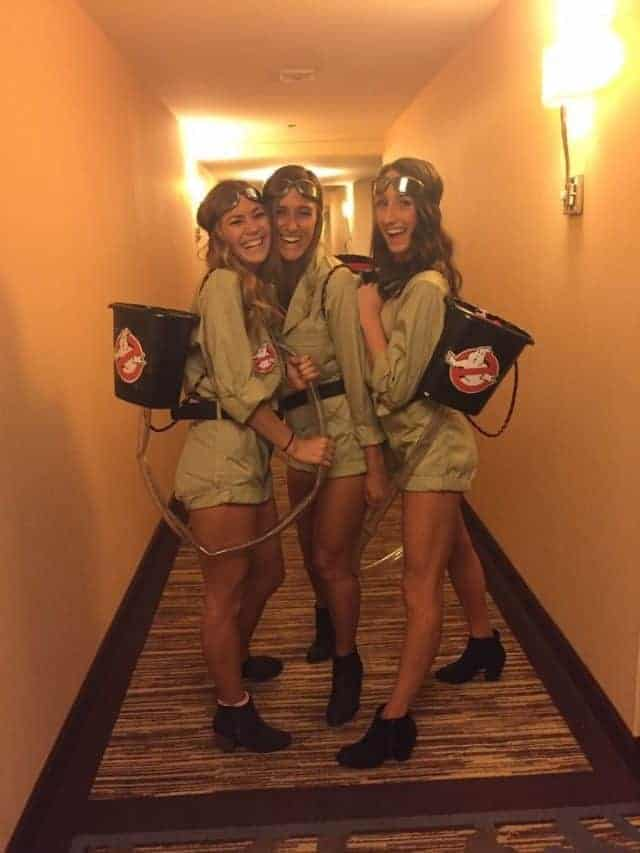 Three women wearing matching Ghostbusters jumpsuit costumes with DIY proton packs.