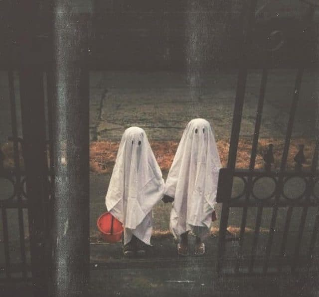 Two individuals wearing classic ghost costumes made of white sheets with eye holes.