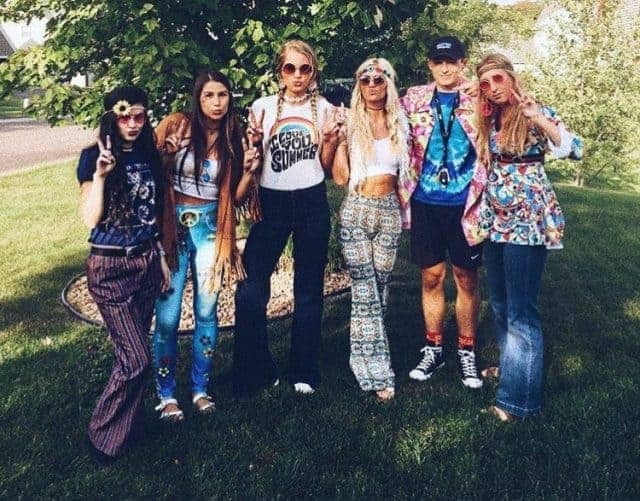 A group of friends wearing flower-power hippie costumes with paisley, tie-dye, and psychedelic prints.