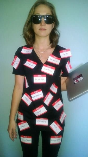 A woman wearing an identify theft gag costume with name tags taped to a matching black outfit and laptop.