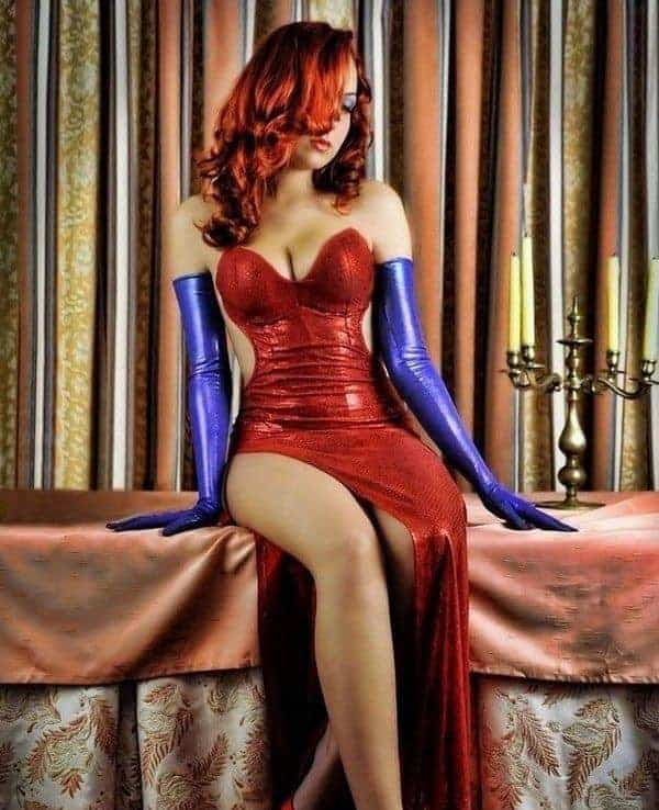 A woman wearing a Jessica Rabbit costume with the red sparkly evening gown and full purple gloves.