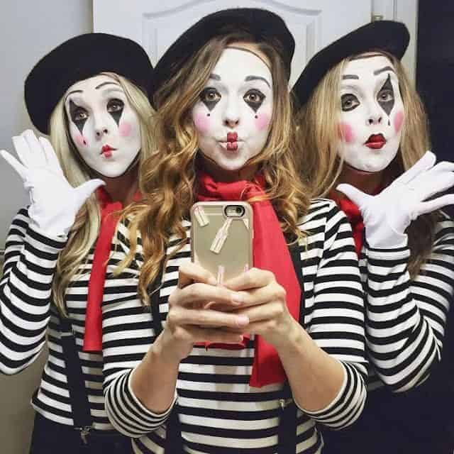 Three women wearing matching French mime costumes with black and white striped tops, red scarves, black berets, and suspenders.