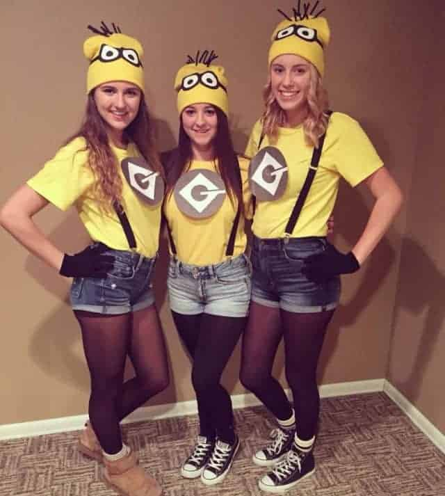 Three women wearing matching Minions costumes with the yellow shirts, denim shorts, matching beanies, and suspenders.