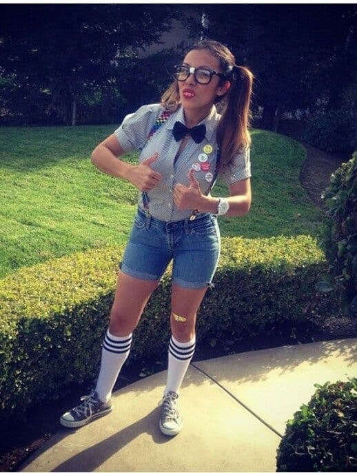 A woman wearing a cliché nerd costume with statement buttons, a bowtie, and matching horn-rimmed glasses.