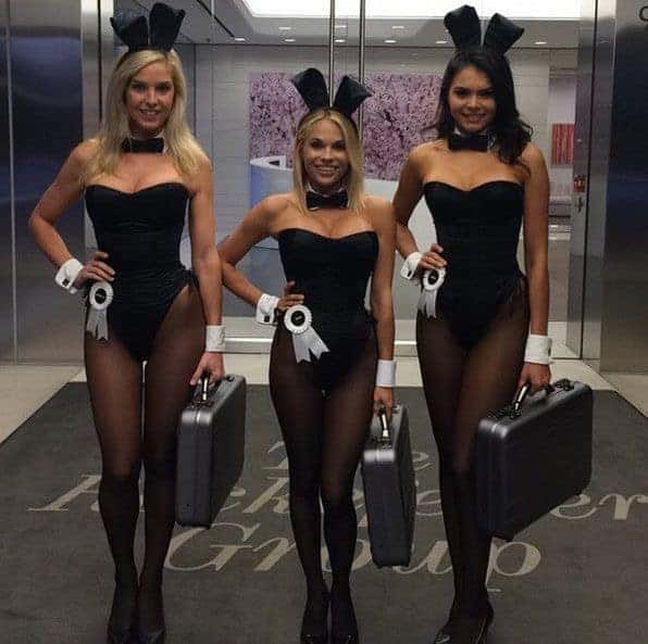 Three women wearing Playboy bunny costumes with matching ears and briefcases.