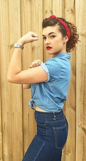 A woman wearing a Rosy the Riveter Halloween costume with the distinguishable red headband and denim top with rolled-up sleeves.