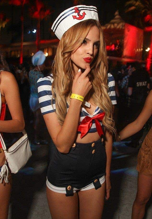 A woman wearing a sailor costume with a blue and white striped crop top adorned by a red ribbon and matching hat inspired by the Netflix series Stranger Things.