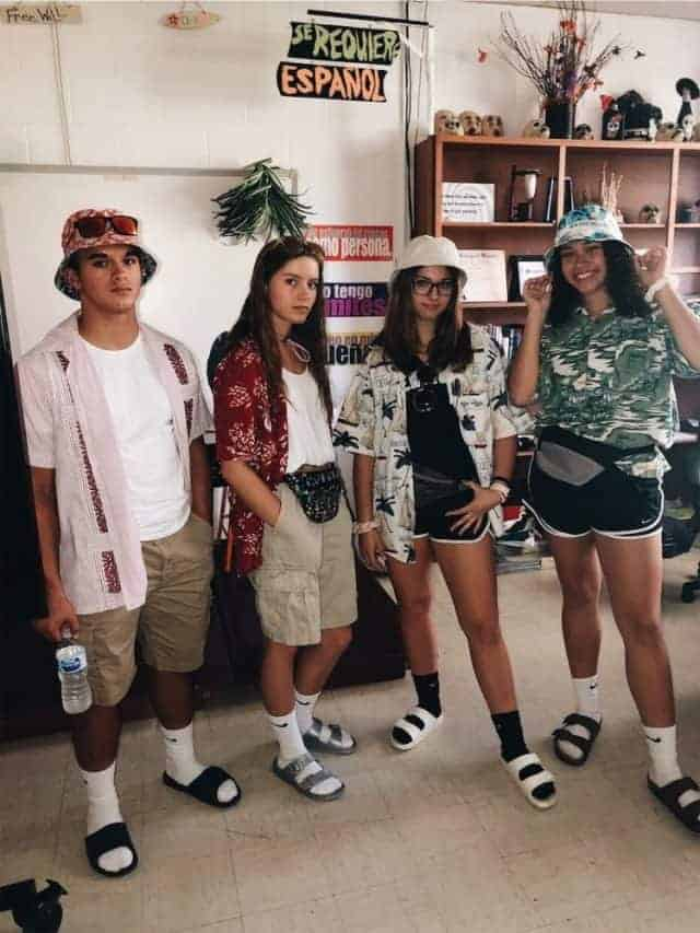 A group of friends wearing cliché tourist outfits with the necessary bucket hats, Birkenstocks with socks, and fanny packs.