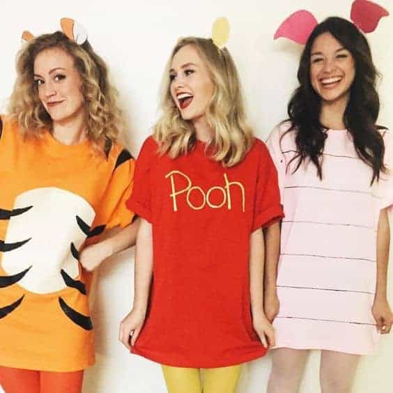 Three women wearing matching Tigger, Pooh, and Piglet costumes from Disney's Winnie-the-Pooh.