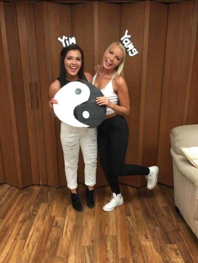 Two women wearing yin and yang costumes with alternating black and white outfits and a yin and yang symbol.