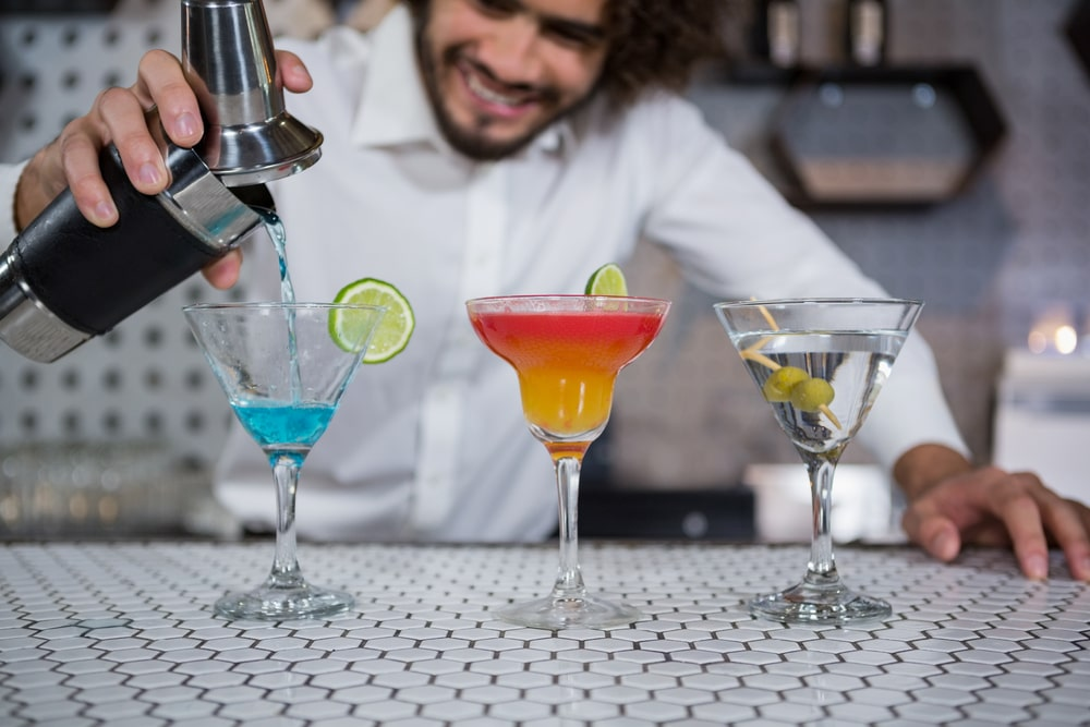 A bartender pouring cocktails.