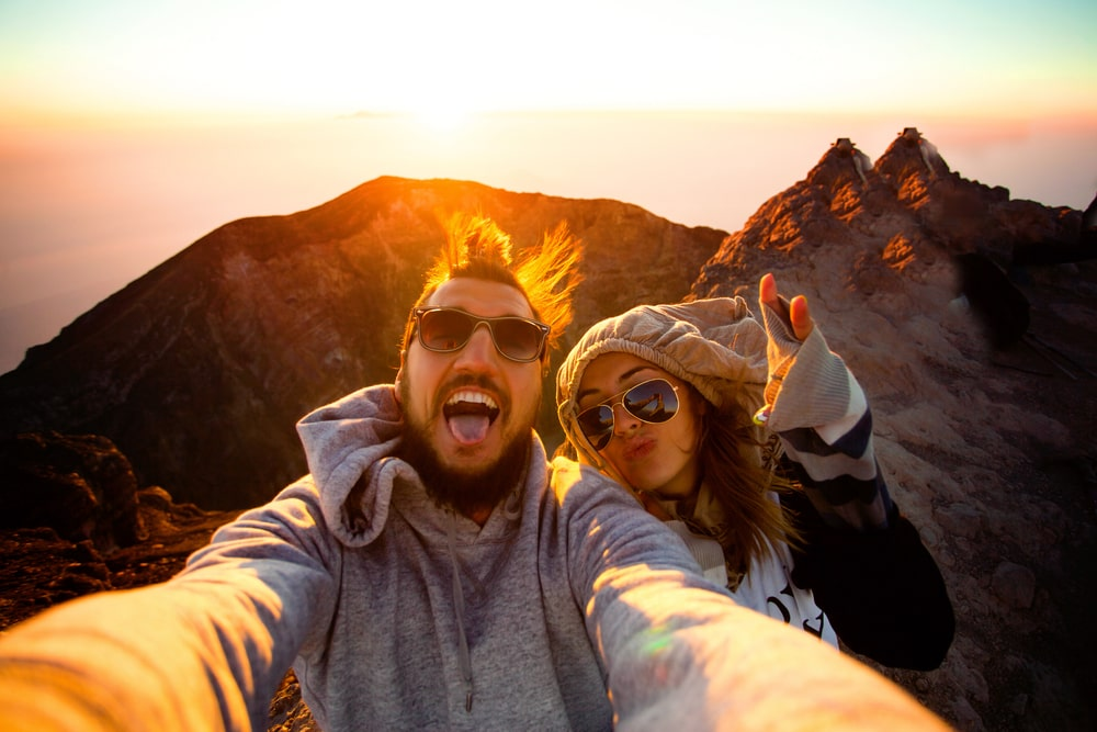A couple having fun on a hike during sunrise.