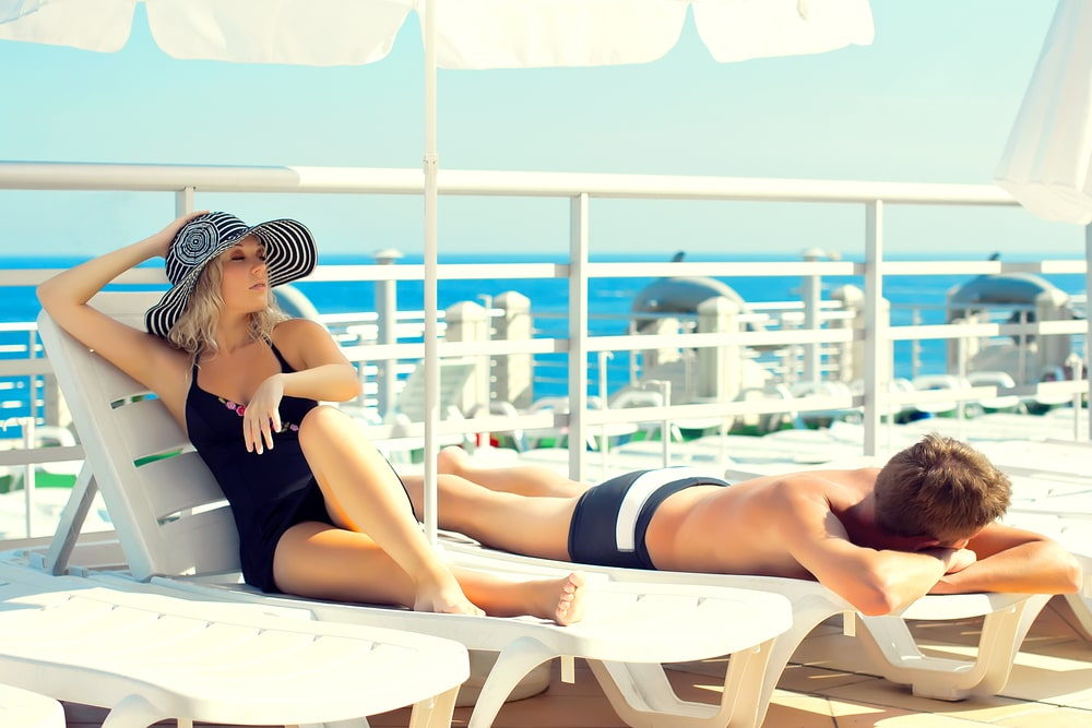 A couple relaxing and sun bathing while on a cruise.