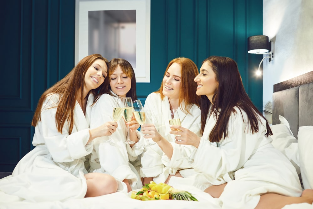 A group of young women having fun in a hotel room.