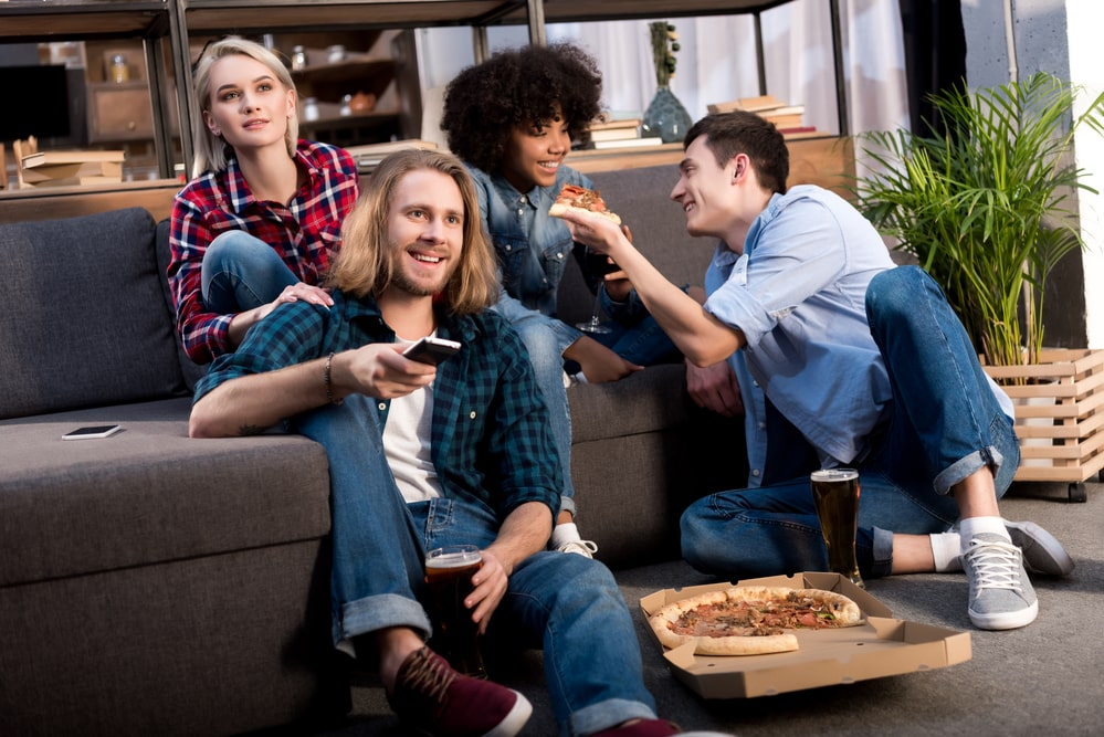 A group of friends watching TV and eating pizza.
