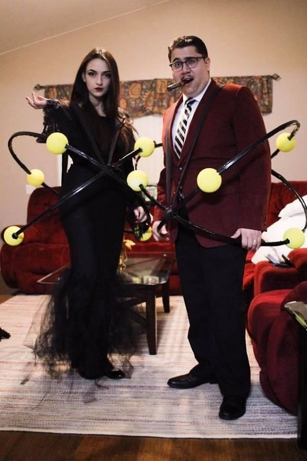 A woman and a man in a Halloween costume that is a combination of Morticia and Gomez Addams and atom models.