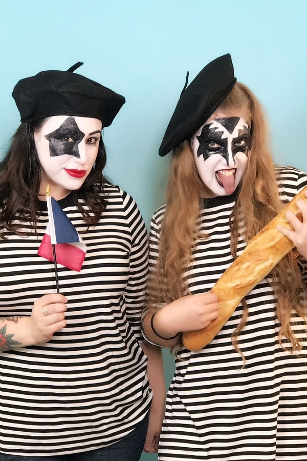 Two women wearing a Halloween costume made of a striped blouse, beret, French flag, baguette, along with face paint inspired by the band Kiss.