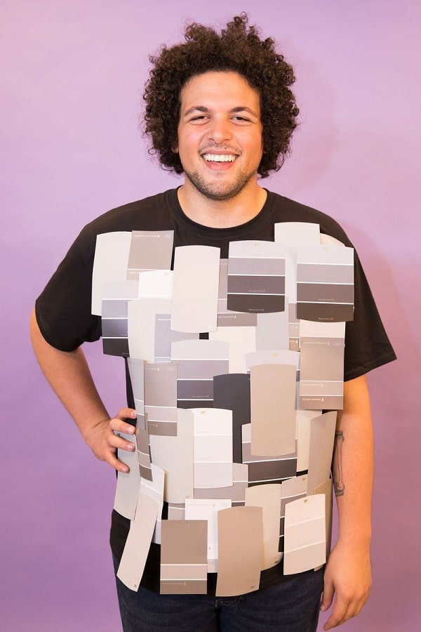 A man in a Halloween costume dressed in a black shirt with various grey color palettes taped on the front.