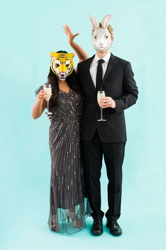 A woman with a tiger mask and a man with a rabbit mask, dressed in formal attire for Halloween.