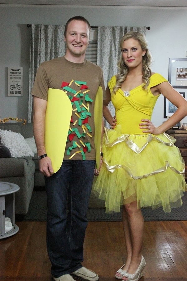 A man dressed as a taco and a woman dressed as Belle for Halloween.
